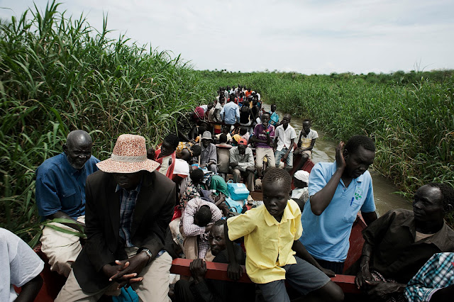 Minkaman, South Sudan, 2014 - John Mamer (left, in hat), on the way back to his old home in Bor. The journey on the River Nile on a barge takes two-three hours depending on the current. John has only been back to Bor very few times since he and the family fled to Minkaman.