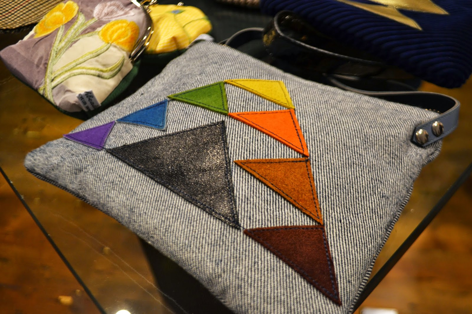 A grey handbag with triangles in various colours sewn to the front