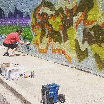 Man spray painting street art on a wall.