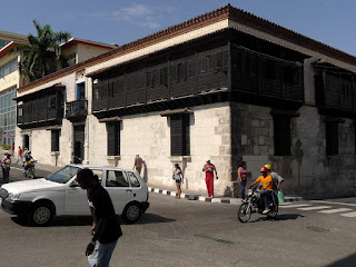 Santiago de Cuba, Parque de Céspedes, Casa de Diego Velázquez. Unteres Stockwerk aus großen Blöcken gemauert, oberes Stockwerk von dunkelbraunen Holzgittern dominiert.