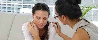 Mujer recibiendo ayuda para superar la pérdida de un ser querido. Ambas visten de blanco y la profesional tiene su mano puesta en el hombro de la paciente.