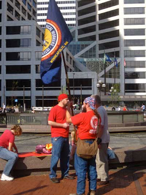 Three guys in red t-shirts with an IBEW flag