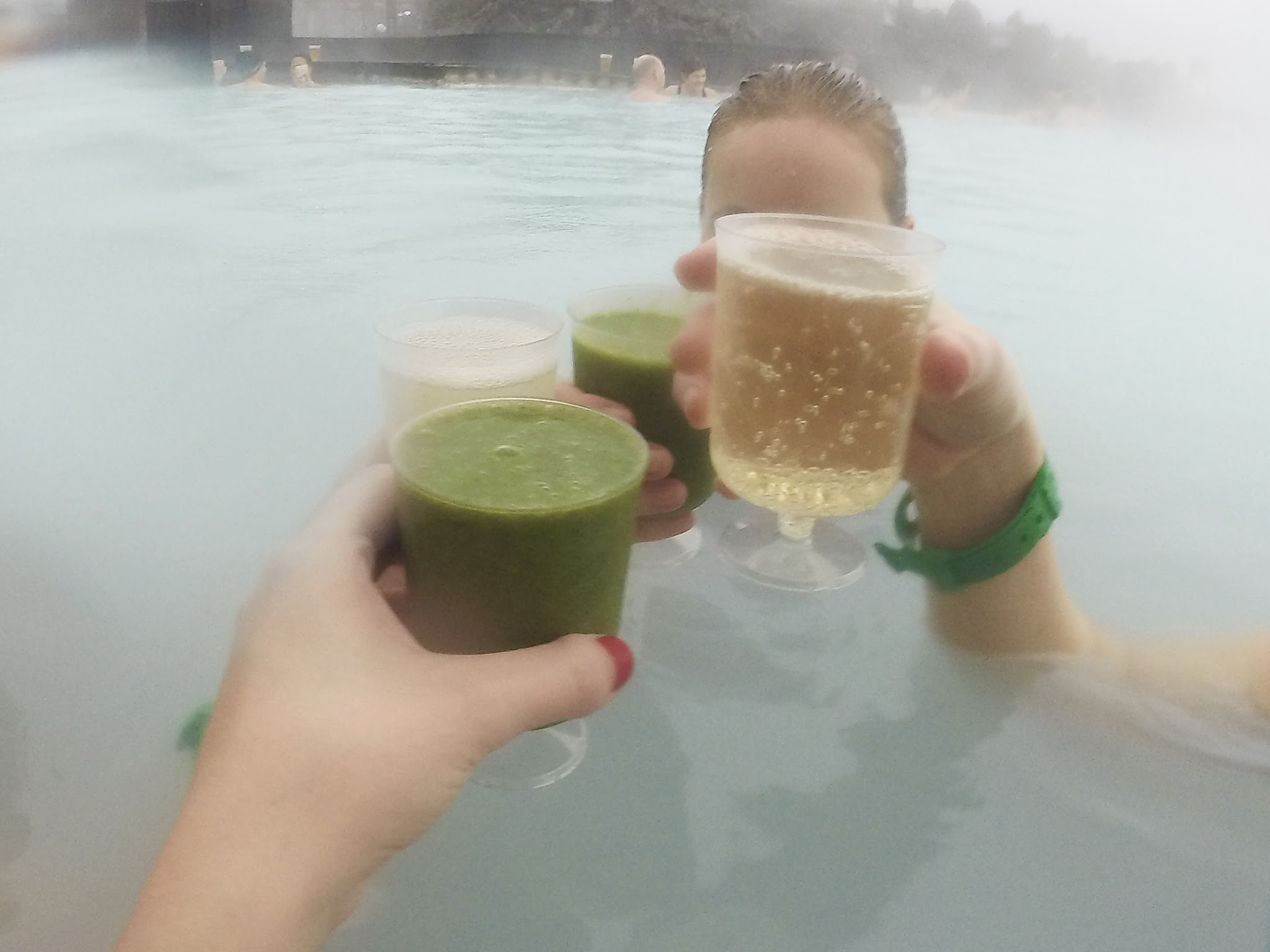 two glasses of prosecco and two glasses of green juice being clinked together above blue water with steam rising