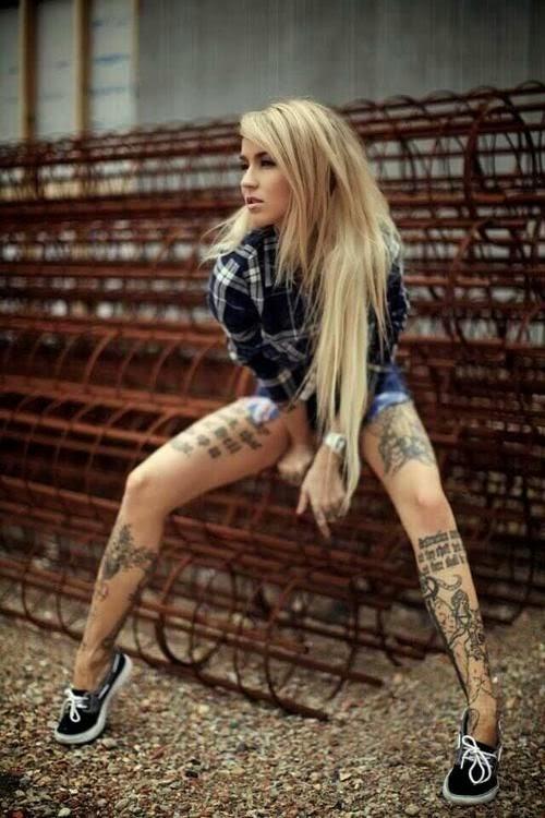 chica con el pelo rubio muy largo sentda en una obra, lleva pantalones cortos y bambas con camisa a cuadros  y tatuajes en las piernas