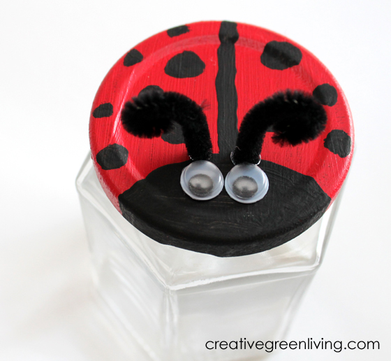 Jar lid painted like a ladybug to make an easy bug catcher craft. Ladybug jar lid has googley eyes and entennea.