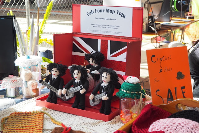 "A closer view of the Fab Four Amigurumi in their red stage box. The sign above says ""Fab Four Mop Tops"". To the left of the red box one can see broomstick needles sticking up from a vase. To the right one can see the green crocheted jar cover which has a Father Christmas applique on top. Further right is the orange handwritten sign ""Crochet hats for sale"""