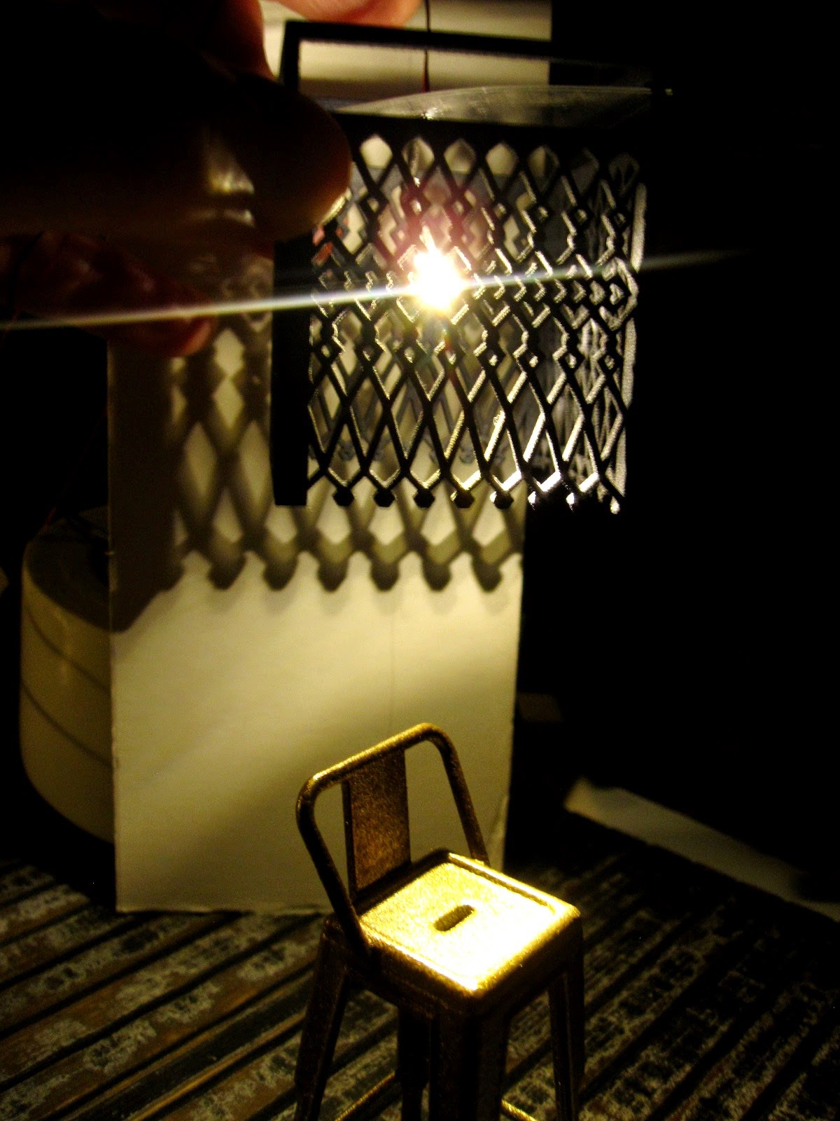 Modern dolls' house miniature scene in progress, with a copper-coloured cafe bar stool in the dark with a geometric-design light shade above, casting patterns on the wall.