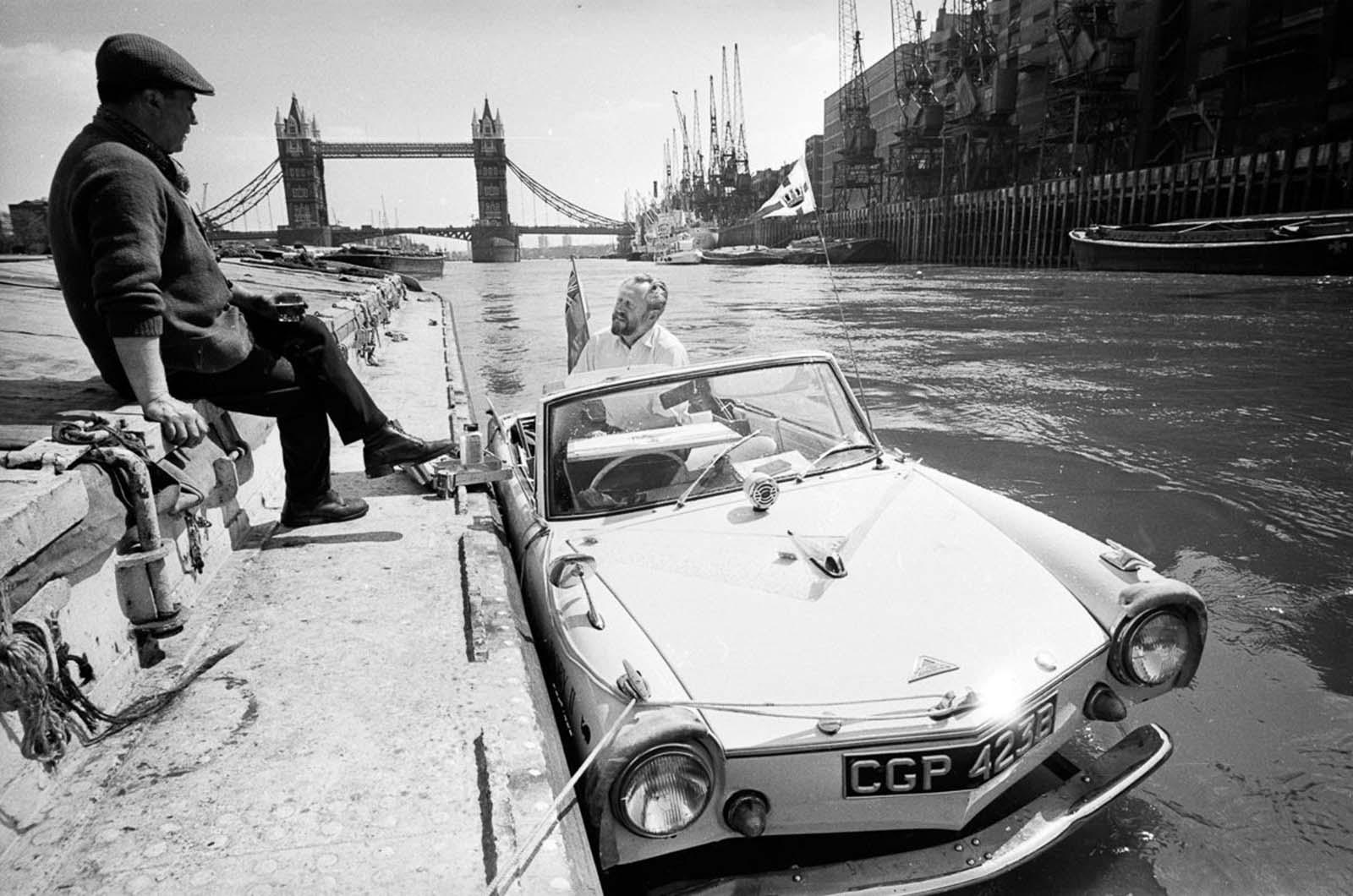 Artist John Worsley docks his Amphicar near Tower Bridge in London. 1966.
