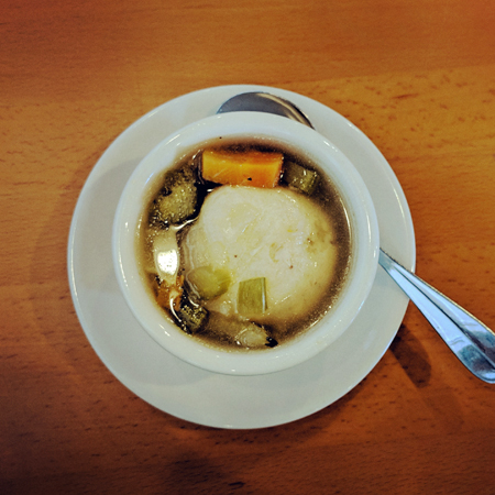 image of a cup of matzo ball soup, featuring one large matzo ball in broth with chopped carrots and celery