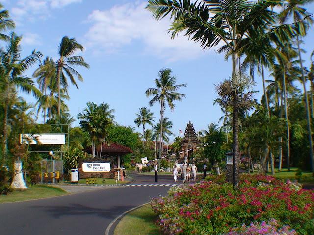 На фото - пальмы, шлагбаум, храм на острове Бали, Индонезия