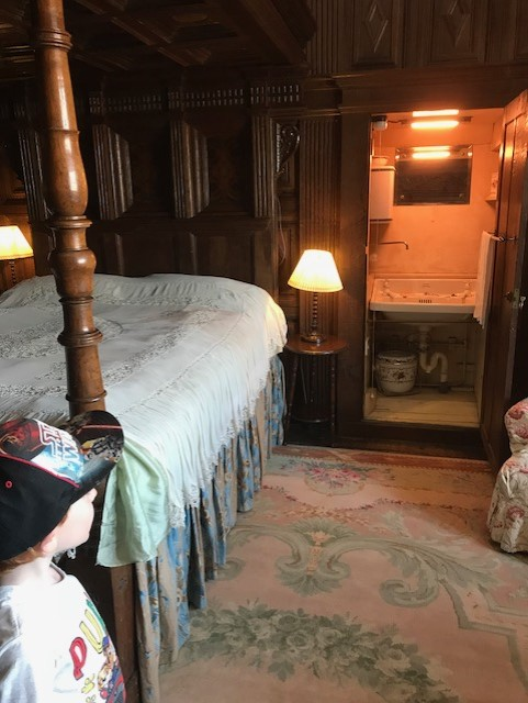 Four poster bedroom with an open wardrode which is housing a sink