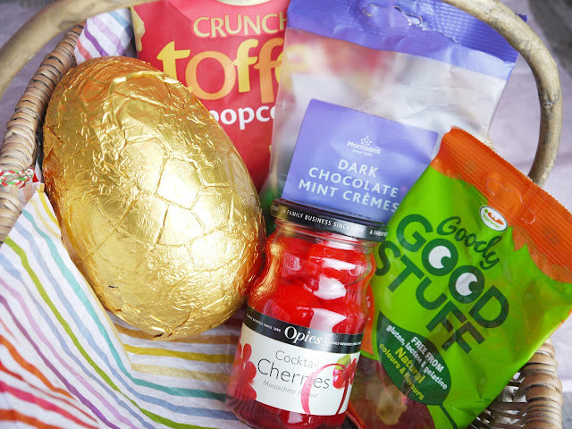 an easter egg in gold foil, packets of gummy bears, mint cremes, and popcorn, and a jar of cocktail cherries