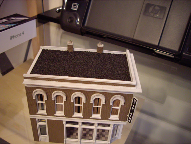 Sand covered roof of a completed DPM The Other Corner Café kit modeled as a bank