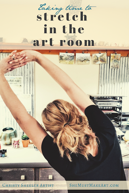 Taking time to stretch in the art room by Christy Sheeler Artist.  Artist stretching with arms linked above her head.