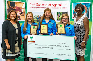 Group of 4-H'ers holding check with Extension leaders