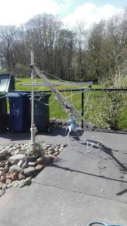 vetrom zlomený vešiak na prádlo, v pozadí smetné koše