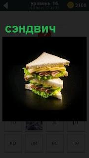Приготовленный сочный бутерброд сэндвич лежит на темном столе