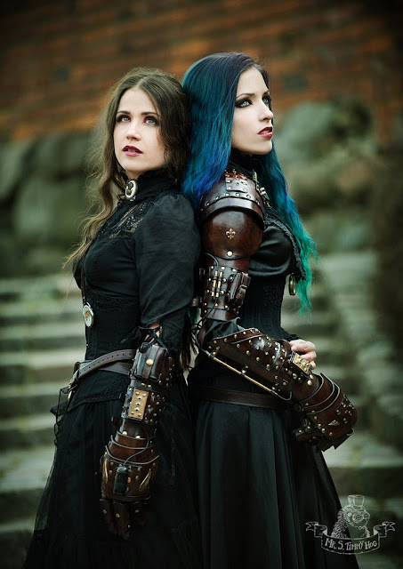 Steamgoths in gothic steampunk clothing (long black dresses, corsets, cameo chokers) with leather gauntlets