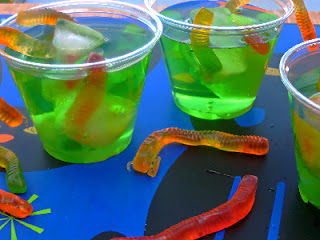 3 cups of green drink with gummy worms in them