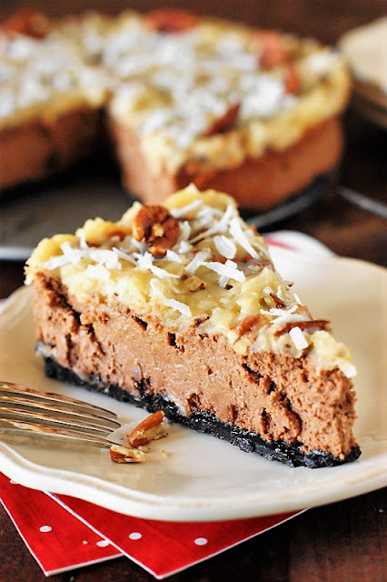German Chocolate Cheesecake Image ~ Love German chocolate cake?  Give German Chocolate Cheesecake a try!  Creamy chocolate cheesecake is baked atop an Oreo crumb crust and topped with the classic coconut-pecan topping from the ever-popular German chocolate cake.  The result is one very tasty cheesecake, indeed.