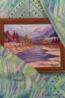 Photograph of a framed landscape painting wrapped in a knit blanket for protection while moving by Cramer Imaging