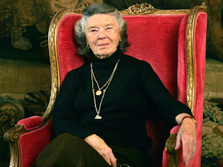 Rosamunde Pilcher sits in a fancy red chair.