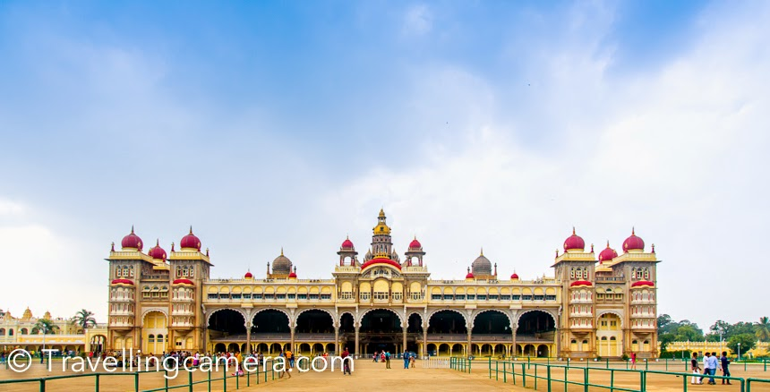 While coming back from Kannurto Bengaluru , we planned stop at Mysore Palace. We didn't stop for lunch on the way and thought of taking a break at Mysore and have some light lunch. It's a historical palace in the city of Mysore in Karnataka, southern India. It is the official residence and seat of the Wodeyars — the Maharajas of Mysore, the former royal family of Mysore, who ruled the princely state of Mysore from 1399 to 1950.  Asked our taxi driver to drop us at the entry gate of Mysore Palace and park for next 1 hr.There is a dedicated parking area adjoining Mysore Palace campus. There is another huge parking across the road and lot of buses were parked in that parking.  Ticket counter was empty, so it hardly took 5 minutes for us to enter into the campus. There was no one at the main entry to check out tickets. Entry ticket for one person costs 40 Rs and there is no ticket for camera. I specifically asked for camera fees and surprised to know that no fees is charged for cameras.After entering into the Mysore Palace campus,  we thought of taking a round of this huge compound. The palace houses two durbar halls and incorporates a mesmerizing and gigantic array of courtyards, gardens, and buildings. The palace is in the central region of inner Mysore, facing the Chamundi Hills  on the other side. There is lot of open space around the main palace. There is a temple around one of the corners of Mysore Palace.The Palace of Mysore is also known as the Amba Vilas Palace. After walking outside the palace, we reached the entry which takes you inside the palace. We needed to take out shoes. As we reached the counter to deposit our shoes, the guy standing there refused to give us a token and assured that we need not to worry :). Anyways, we moved on and stood in the queue.As we reached the security check, we were notified that cameras are not allowed inside and you need to keep it somewhere. Now I got to know that why there was no fees for camera but the person at ticket counter didn't bother to inform us about that. After spending 5 minutes in discussions with security folks, we got to know that a counter is there outside the compound where camera can be deposited. This was again a task of 15 minutes to take shoes back, deposit camera and then come back.Now we decided to directly go back to our cab and continue with our next journey towards Bengaluru. As we headed back to the shoe counter, the man at the counter asked for 'tip' and then gave us our shoes. Isn't it weird?Mysore is also popularly the City of Palaces. There are about 7 palaces inclusive of Mysore Palace. Now we didn't have to explore more in Mysore City. Probably we shall go there again sometime. I have also heard a lot of the Dussehra celebrations in Mysore, so let's see if I plan for it in future.To know more about the history and architecture of Mysore Palace, check out. It seems that Mysore Palace is now one of the most famous tourist attractions in India, after the Taj Mahal, and has more than 3,000,000 visitors annually. But not sure if I should compare it with Taj or not.