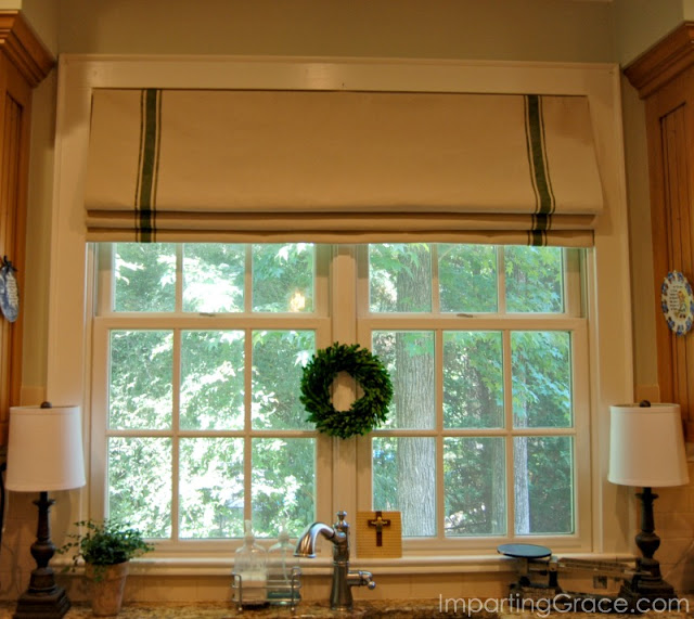 Paint a dropcloth to resemble a grainsack and create a faux Roman shade with tension rods