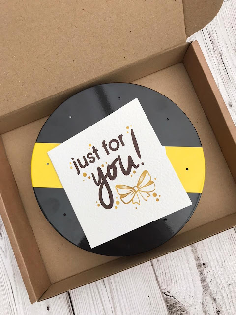 An open box with a tin and a card marked just for you