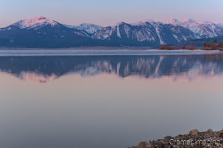 Cramer Imaging's professional quality landscape photograph of mountains and a cabin reflecting in Henry's Lake at dawn