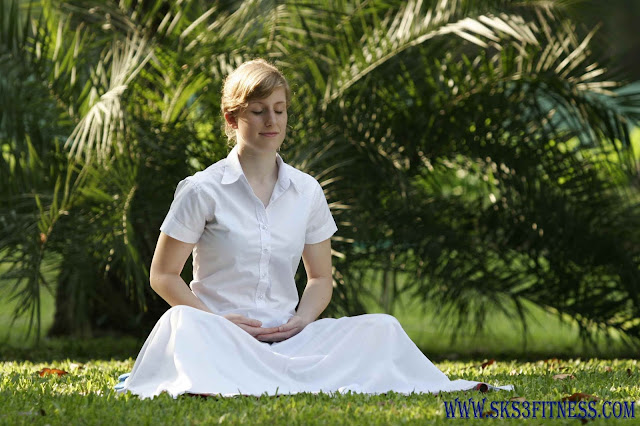 A girl doing Loving kindness meditation in the garden on grass