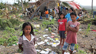 School children in the Philippines contemplate the aftermath of Super Typhoon Haiyan in 2013. Climate change is making tropical storms more intense (Picture Credit:  Pio Arce/Genesis Photos) Click to Enlarge.