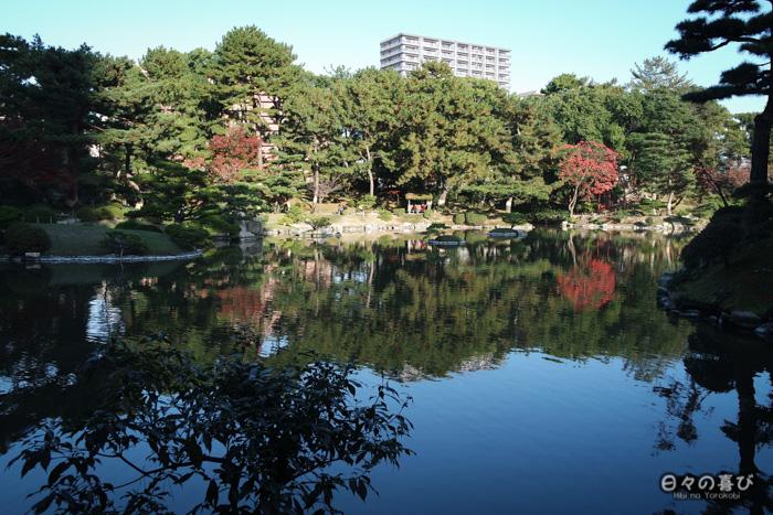 Plan d'eau et immeuble au loin, jardin shukkei-en, Hiroshima-shi