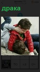 происходит драка между мальчиками на полу