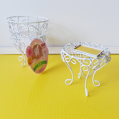 White wire flower pot holder with a one-twelfth scale miniature white wire side table next to it, holding a yellow and white tray.