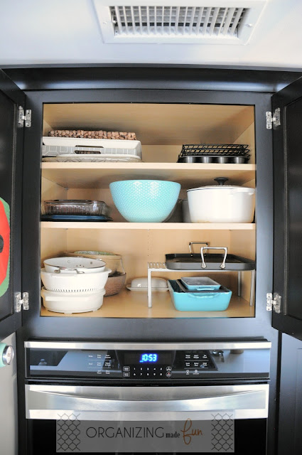 Organized cupboard for trays and serving dishes above double oven :: OrganizingMadeFun.com