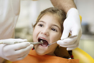 A young girl getting her teeth examined at the dentist in Independence, MO