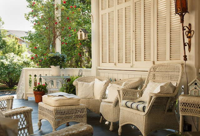 main house back porch with three white wicker chairs and foot stool with cushions and potted plants