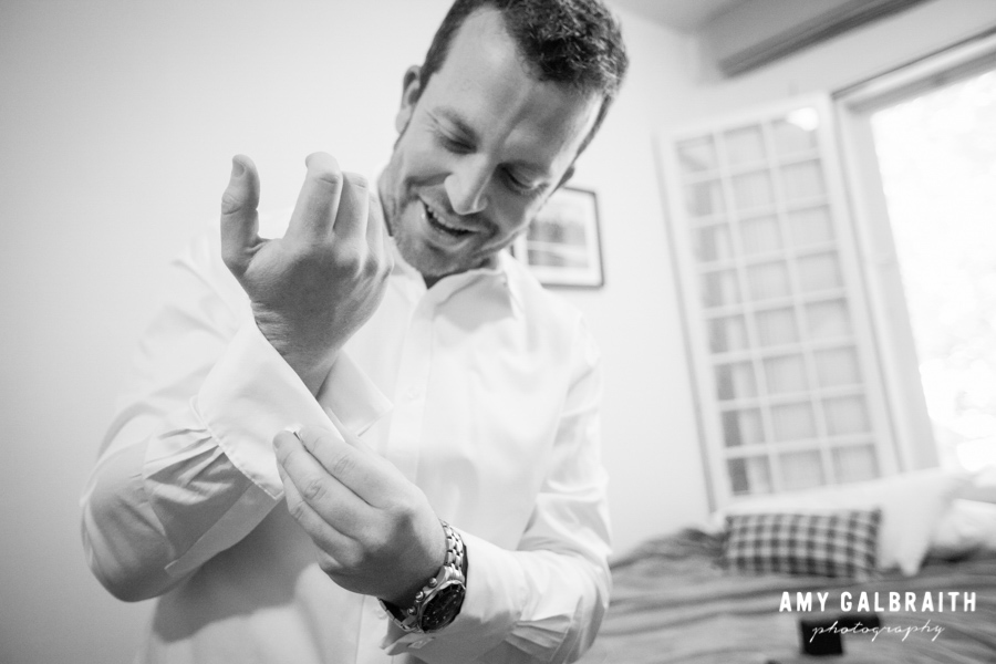 black and white image of groom fixing cufflinks