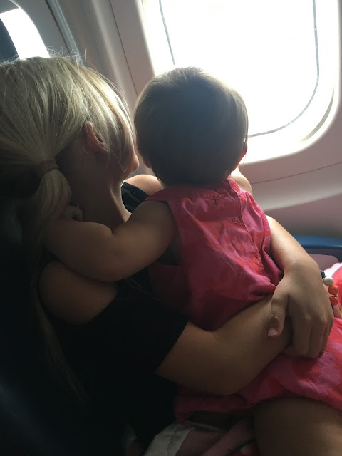 Sisters stare out an airplane window