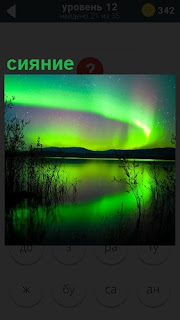 над озером в небе висит северное сияние, отражаясь в воде