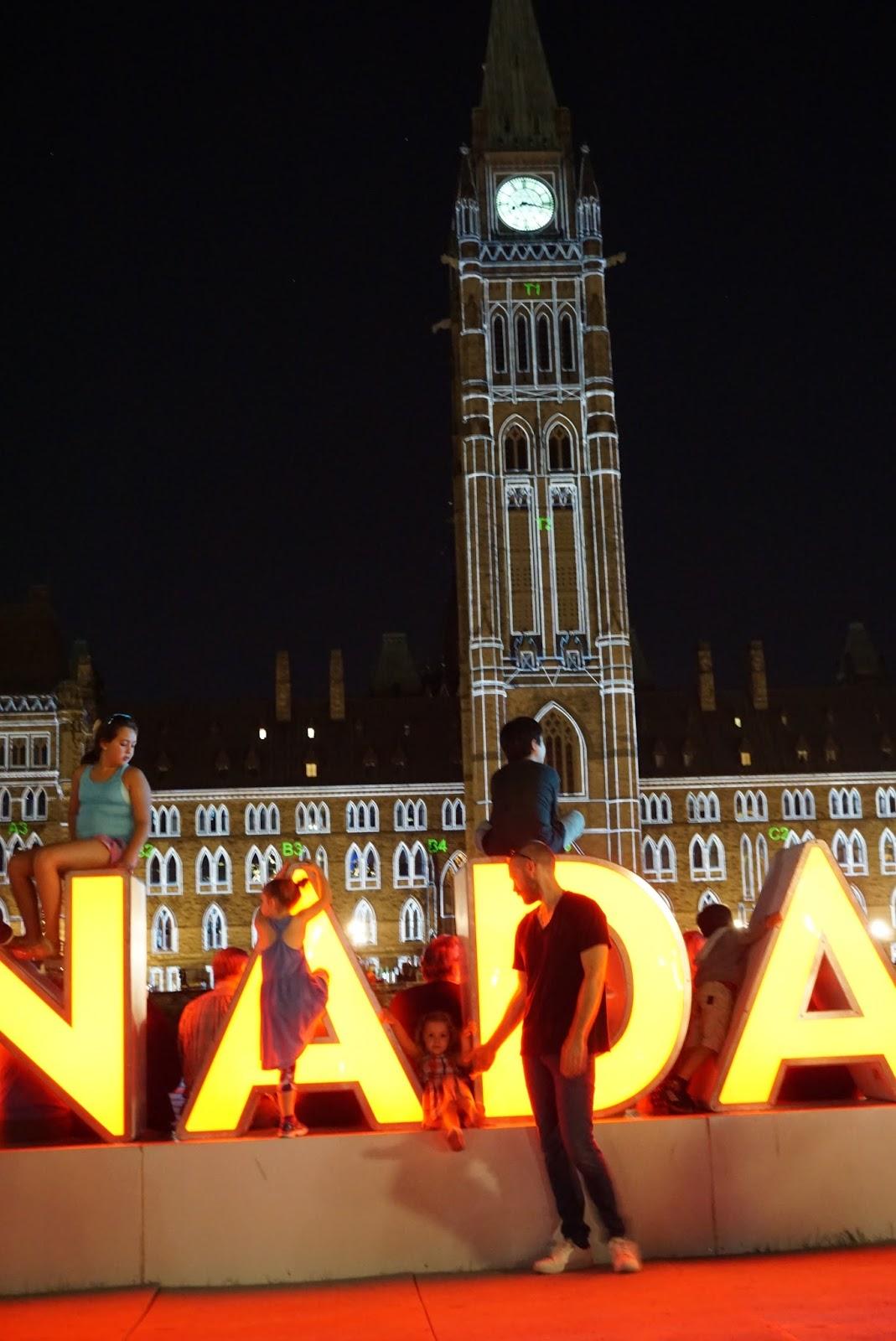 Crianças brincando no letreiro CANADA 150, na frente do Parlamento canadense, em Ottawa