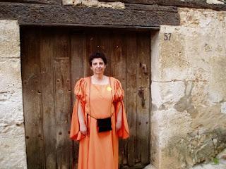 Una foto mía de hace diez años ataviada con un traje seudomedieval naranja y ante una puerta vieja de una casa antigua