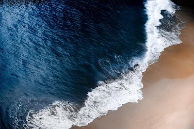 Playa con agua muy azul y espuma
