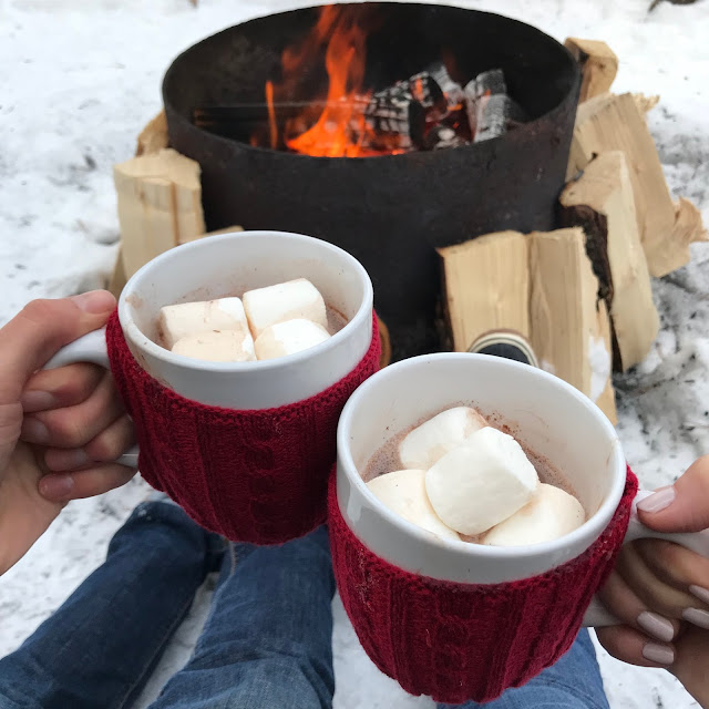Erica Cook and Luke Boyer holding hot chocolates by a fire at Mount Engadine Lodge