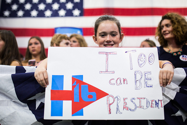 image of a little white girl at a Clinton rally, holding up a handmade sign with the Hillary logo and text reading: 'I too can be president.'