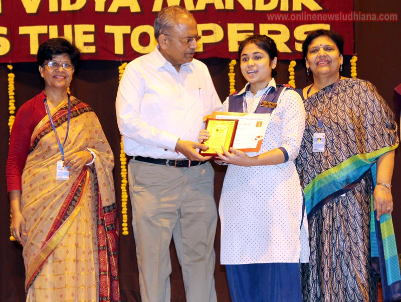 Chief Guest Ashwini Kumar honouring a student during Honouring the Toppers Function at KVM