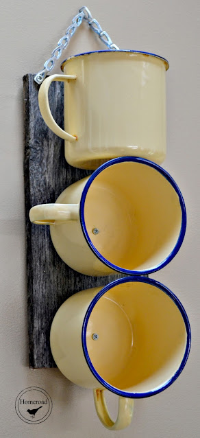 Yellow enamelware mugs screwed to a board