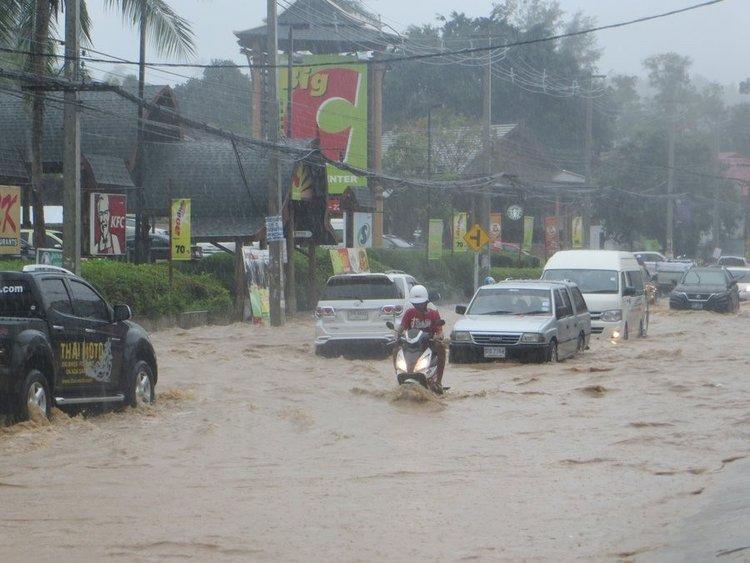 Скутер едет рядом с машинами по глубокой воде