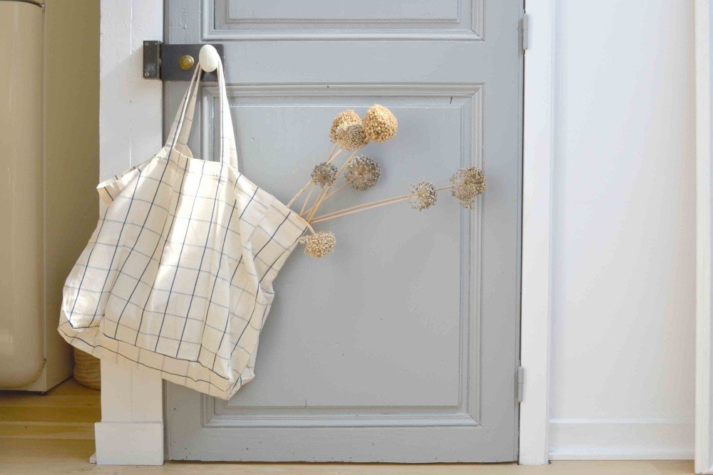 Vintage blue grey pantry door with tote bag in 1650 Marais Paris home of Lucille Gauthier-Braud